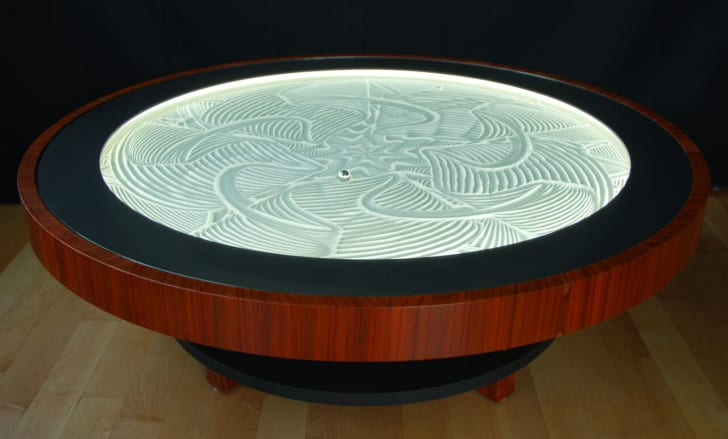 Metal ball carves intricate patterns into sand art coffee table.