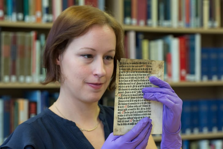 Erika Delbecque holds up the Caxton leaf she discovered in the University of Reading's library archives