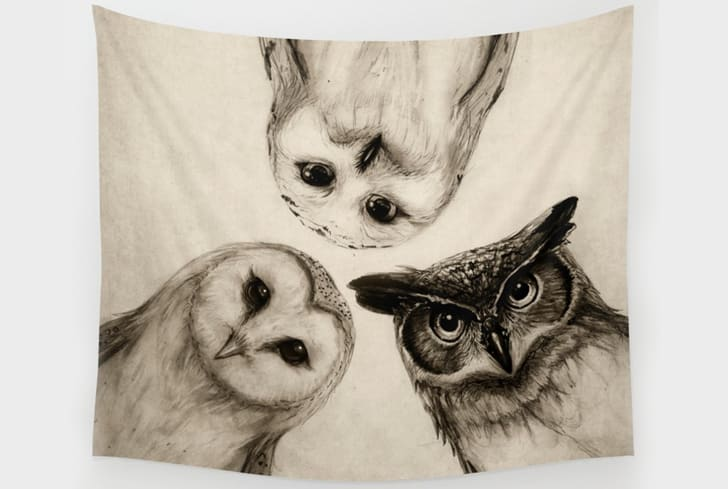 A tapestry with a black-and-white illustration of three owls on it