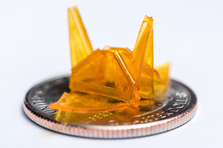 an origami crane made of orange resin sitting on a quarter on a white table
