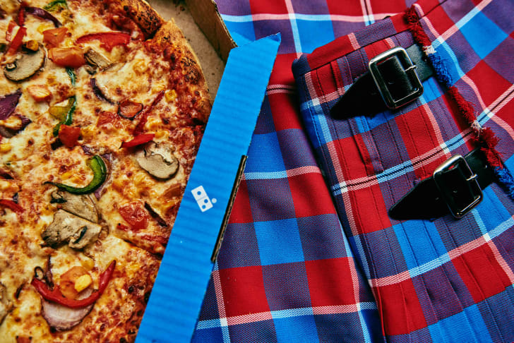 Domino's pizza next to kilt uniform worn by Scottish employees