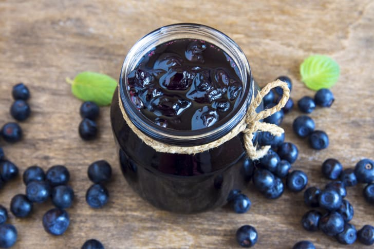 Blueberry jam in jar with berries and leaves over rustic wooden table