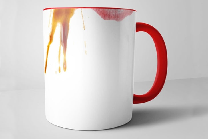 A mug that appears stained with coffee and lipstick
