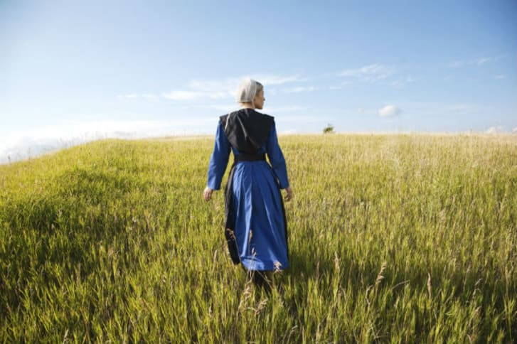 An Amish woman walking in a field
