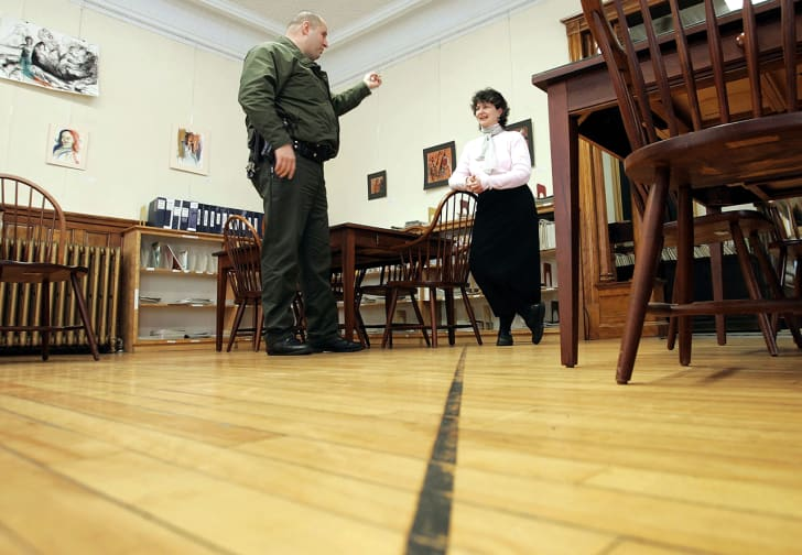 U.S. Border Patrol Agent Andrew Mayer speaks to Nancy Rumery as he stands on the Canadian side of a line on the floor of the Haskell Free Library and Opera House that marks the border between the U.S. March 22, 2006 in Derby Line, Vermon