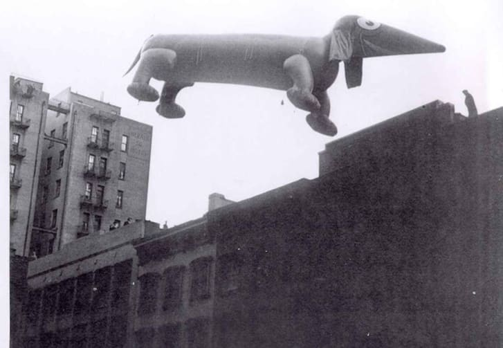 A black-and-white photo of a dog balloon at an early Macy's parade