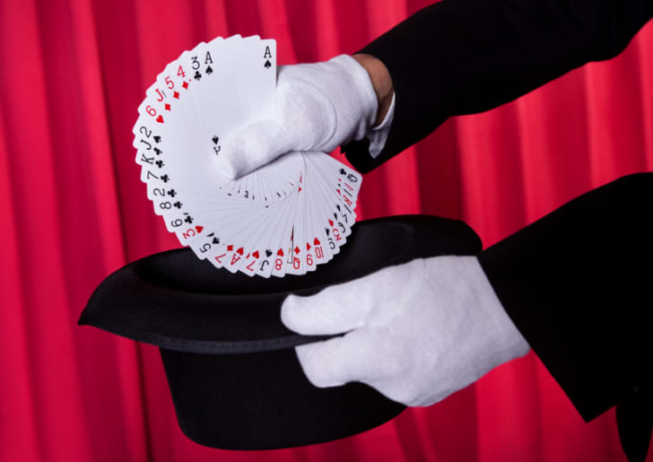 Magician Hand Holding Fanned Deck Of Cards From Hat