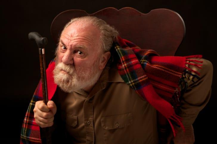 Grumpy old man frowns at the camera