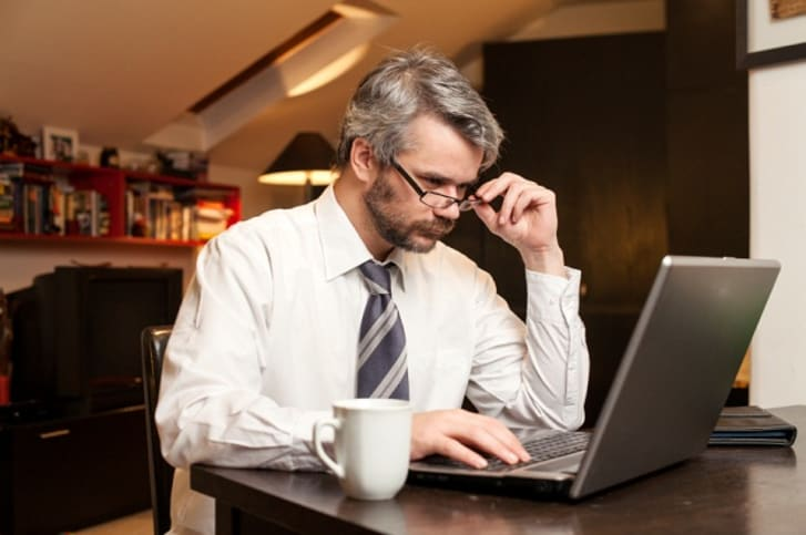 Man drinking coffee and using his laptop