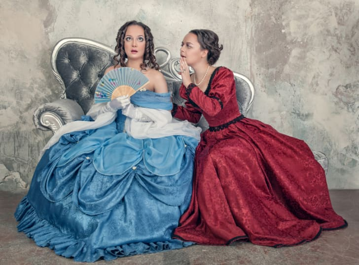 Two women in medieval dresses gossip on the sofa