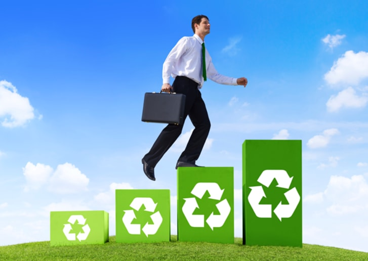 Businessman stepping on green squares with recycling symbols