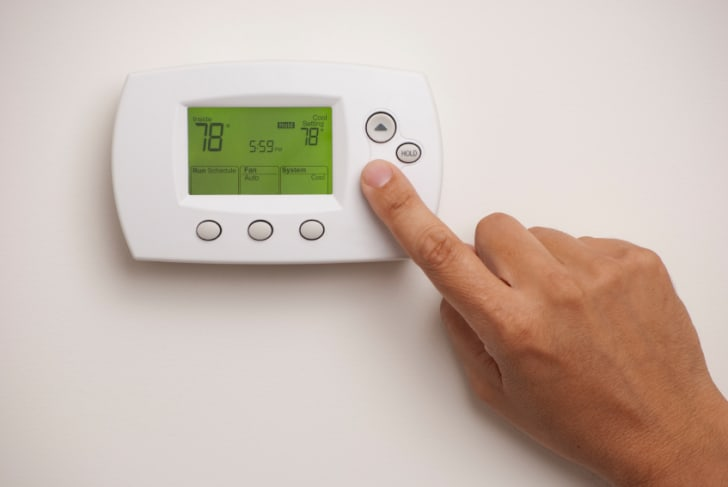 A person adjusting a digital thermostat