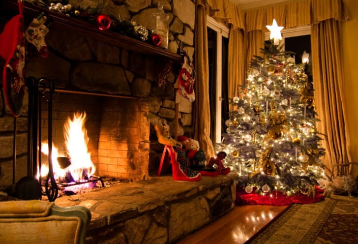 A warm fireplace and Christmas tree in a rustic home