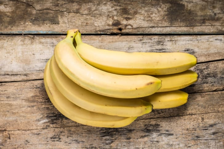A bunch of bananas on a wooden background