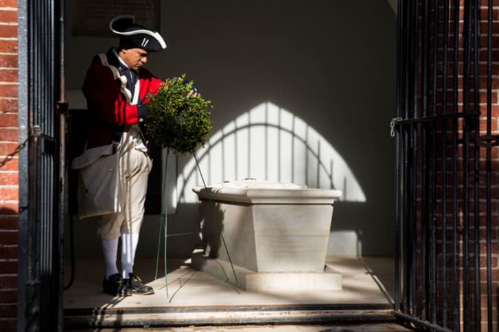 Don Francisco, a reenactor who works at Mount Vernon, places a wreath at George Washington's tomb at Washington's Mount Vernon Estate, February 17, 2014 in Mount Vernon, Virginia
