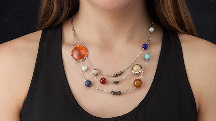 A woman wearing the solar system necklace