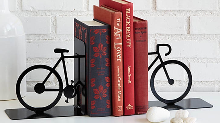 Two bicycle-shaped book ends with four hardcover books between them
