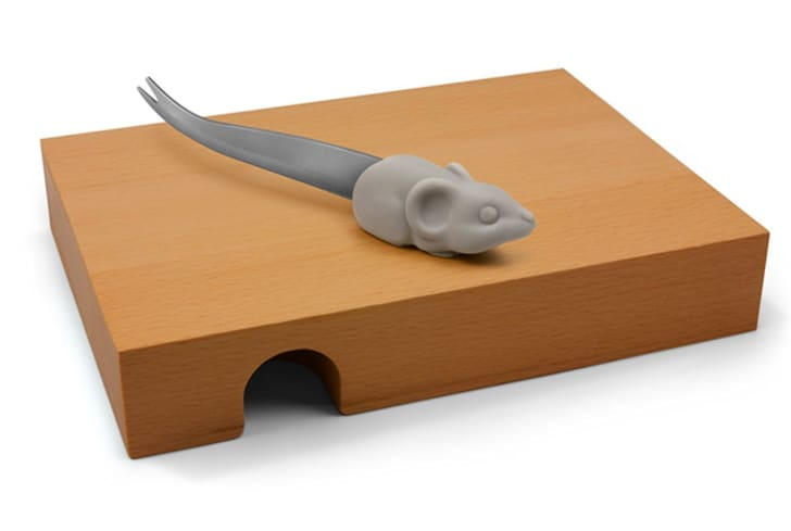A board shaped like a mouse hole with a mouse-shaped cheese cutter on top