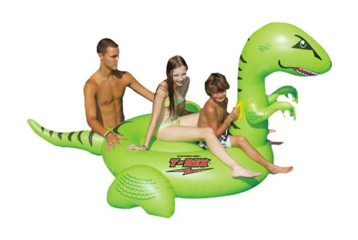 Kids on a dinosaur-shaped pool float
