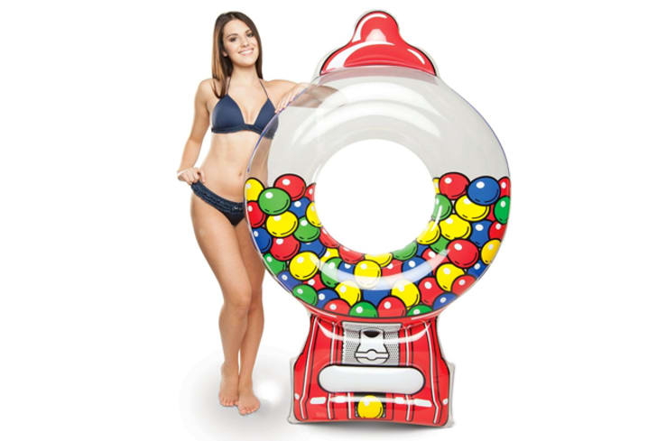 A woman stands next to a pool float shaped like a gumball machine