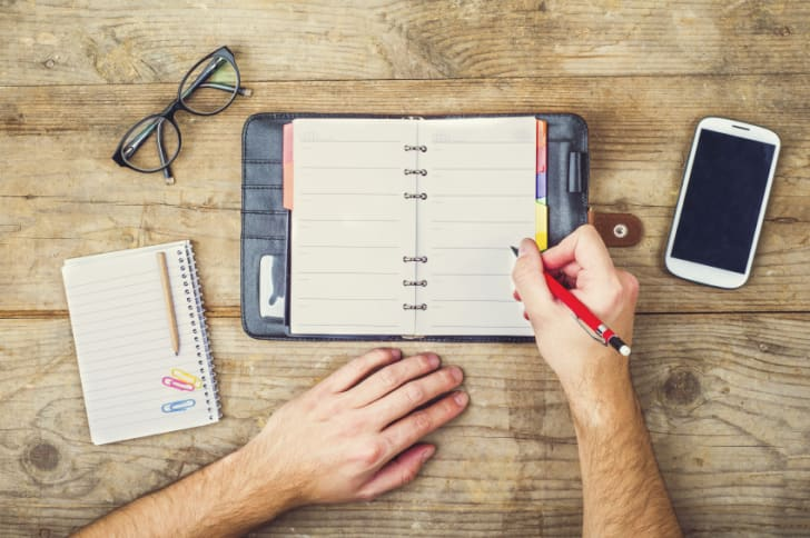 Person fills out daily planner with other work tools sitting on a wooden desktop