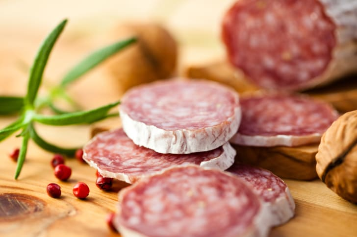 Close-up photo of sliced salami on rustic wooden table