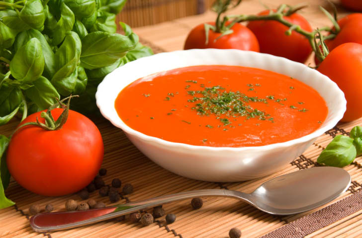 A white bowl full of fresh tomato soup on a wooden table