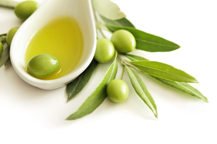 Extra virgin olive oil and olive branch on white background
