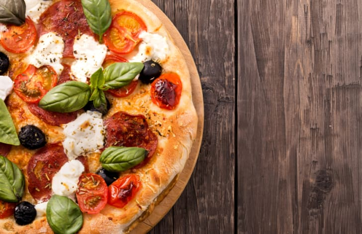 Rustic pizza with salami, mozzarella, olives and basil on wooden table