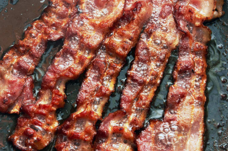 Photo of bacon cooking in a frying pan