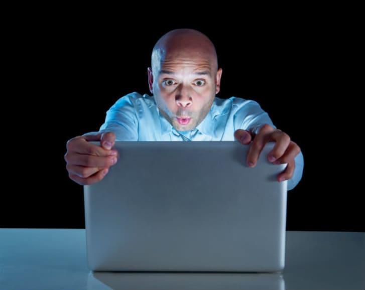 Addict man at computer laptop watching porn internet addiction concept