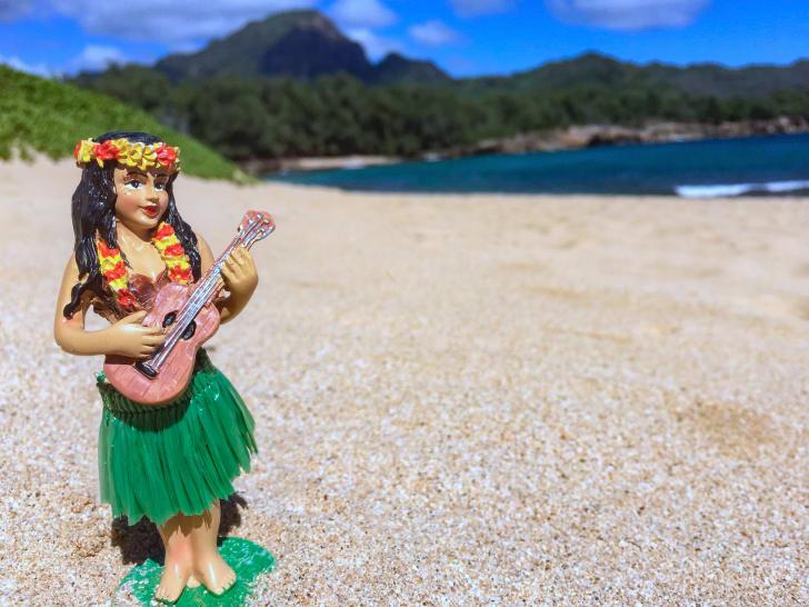 Hula girl sings with her ukulele on a quiet, abandoned beach, Kauai, Hawaii
