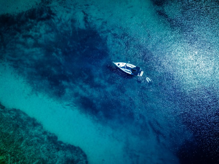 Anchored sailboat in blue waters, view from drone