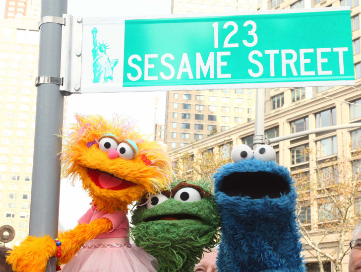 'Sesame Street' Muppets under a street sign that reads '123 Sesame Street'