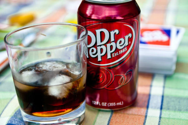 A can of Dr Pepper sits next to a glass