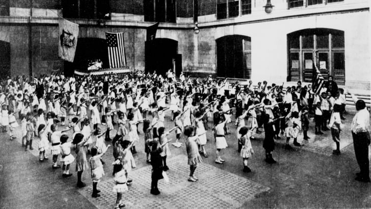 American schoolchildren doing the Bellamy Salute during the Pledge of Allegiance, circa 1915.