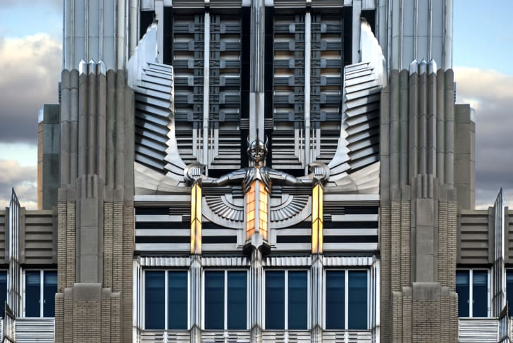 A stainless steel Art Deco winged sculpture on the facade of an embellished building.