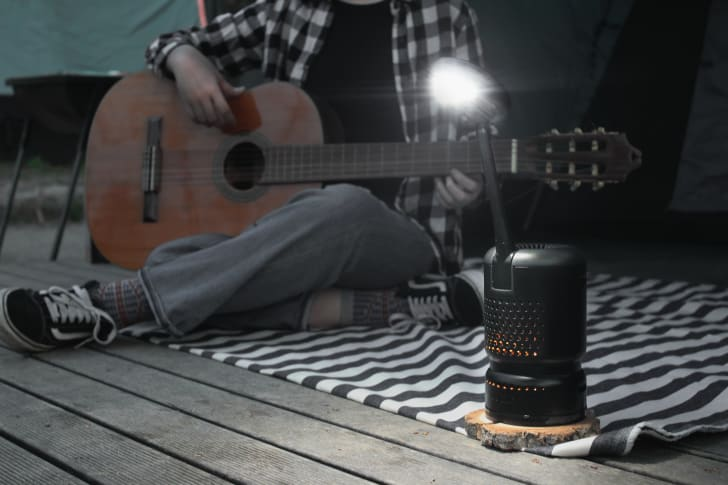 A Lumir K lamp on a deck in front of a person playing a guitar