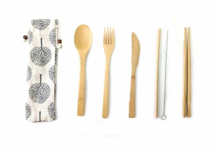 A set of bamboo spoons, knives, and forks on a white background.