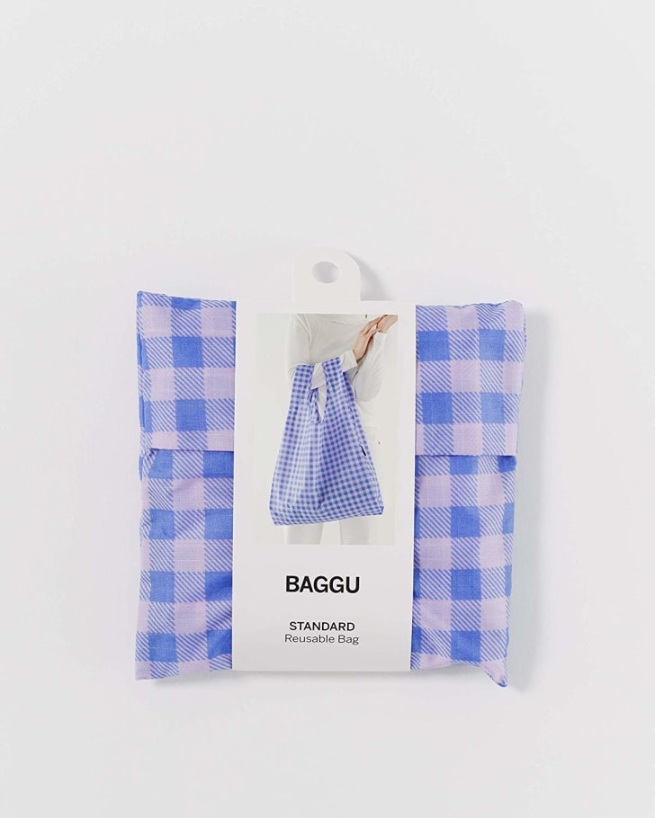 A purple gingham baggu bag folded up in is packaging on a white background.