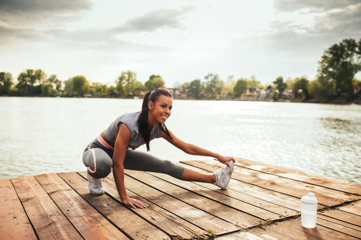 A woman stretching on a dock by a lake.