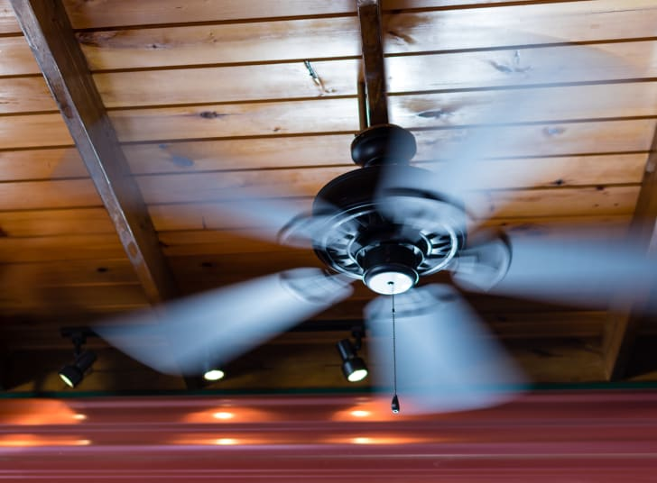 A ceiling fan, its blades blurry with motion, hanging from a wood-paneled ceiling.