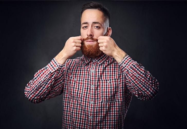 man with red beard on dark background
