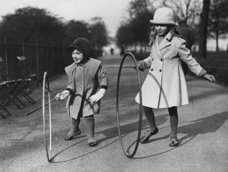 Two young girls rolling hoops in a London park in the 1930s