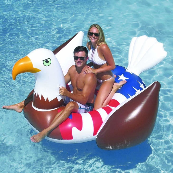 A man and a woman ride a bald eagle pool float