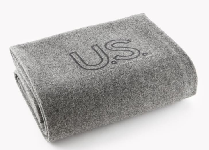 A gray wool blanket with 'U.S.' stamped on it