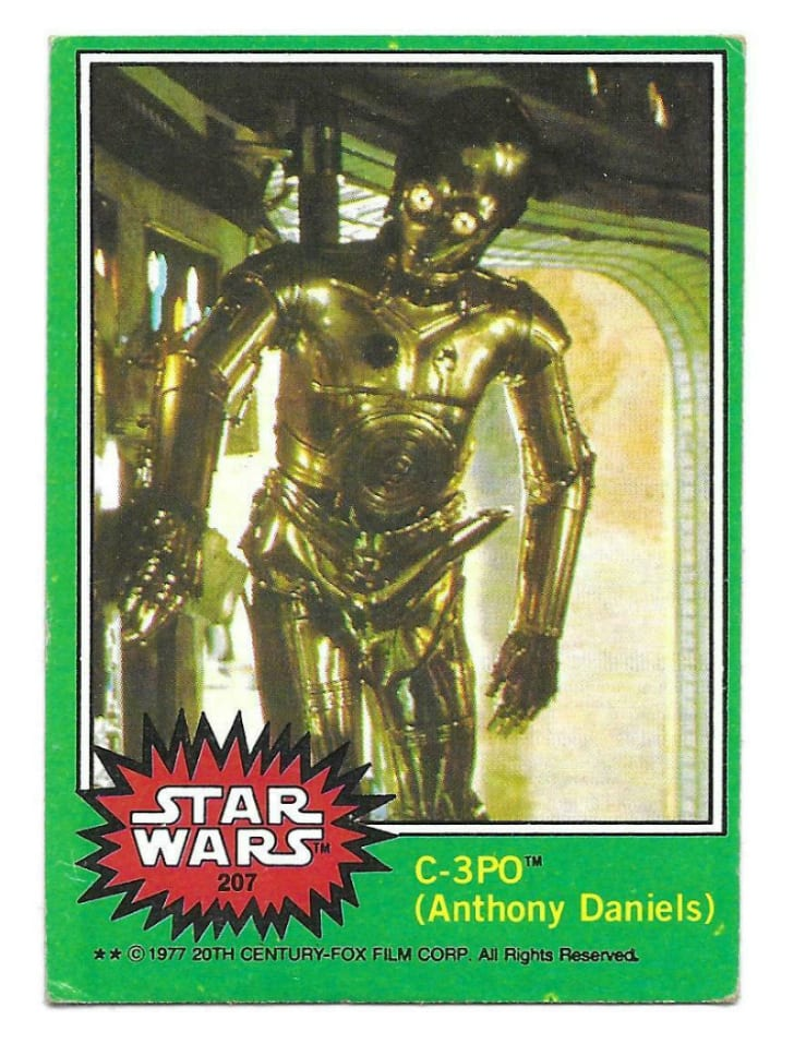 A Topps 'Star Wars' trading card featuring C-3PO is pictured
