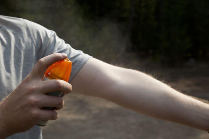 A man sprays bug spray on his arm.
