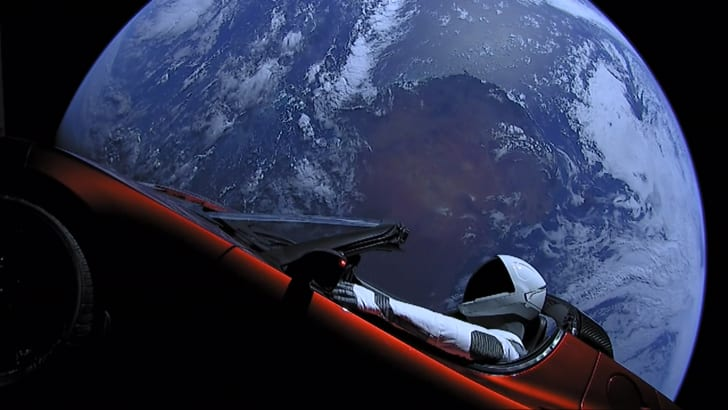 Dummy in Tesla roadster in space with Earth in background.