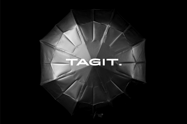 Black umbrella opened up facing towards camera with Tagit print in front, black background